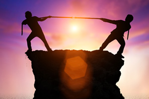 Two people playing tug of war ontop of a rocky platform