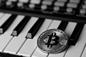 Bitcoin cryptocurrency coin ontop of piano keyboard