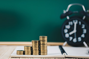 Stack of coins increasing in size infront of chalkboard and alarm clock