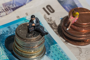 Toy figurines of man and woman on top of coins