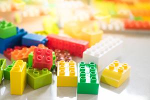 Random coloured plastic building blocks scattered on a floor