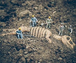 miniature people dig up dinosaur fossil
