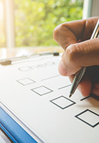 Person holding pen to tick off box on form