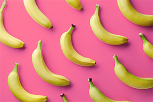 Banana's laid out in pattern on pink background