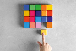 Person fitting yellow block into a multi-coloured puzzle