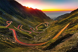 Traffic light trails on windy mountain roads leading towards the sea and sunset