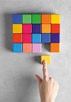 Person fitting yellow block into a multi-coloured puzzle