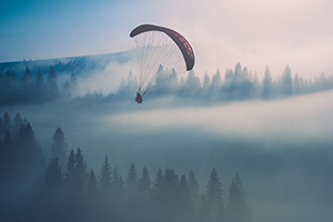 Person paragliding in the misty mountains, causing a risk
