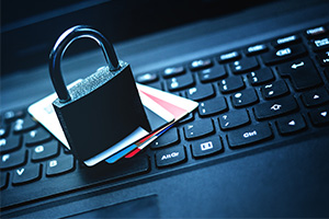 Credit cards ontop of laptop keyboard with a padlock rested ontop for security