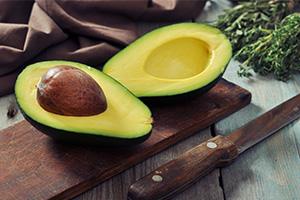 Avocado cut in half on chopping board