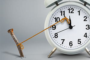 Alarm close minute hand tied to nail in the ground, delay concept