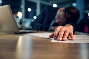 Business person fallen asleep at desk during work hours