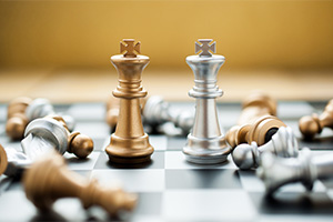Golden and silver king chess pieces standing next to each other, versus