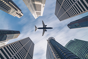 Aircraft flying over tall buildings in city