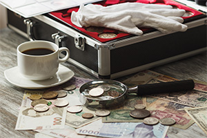 Coin collectors box with gloves, magnifying glass and a cup of coffee