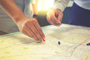 Two people pin pointing journey on a map