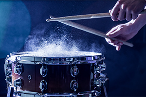 Person beating snare drum with drum sticks