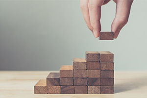 Person building steps with blocks, taking the next step
