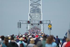 People crossing crowded bridge on foot