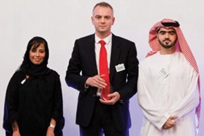 Fatema Al Sayegh, Alastair Fiddes and Faisal Falaknaz accepting on behalf of the Treasury Team at Mubadala