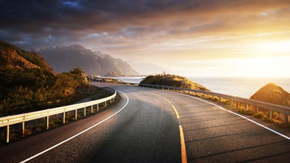 Road on the side of a mountain with the sun rising over the sea