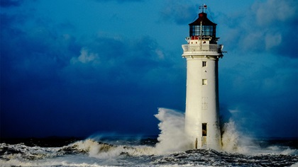 Lighthouse standing with waves crashing into it