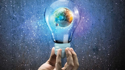Person holding bulb up with the earth inside the bulb