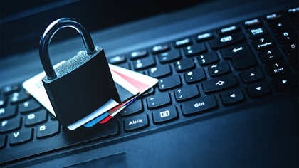 Padlock ontop of credit cards that are laying on a laptop keyboard