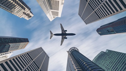 Aeroplane flying over city skyscrapers