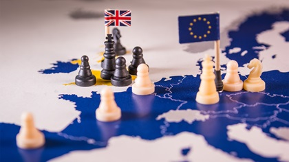 Chess pieces with UK and EU flags on a map of Europe