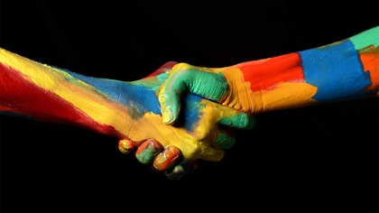 Two people shaking hands covered in different colours of paint