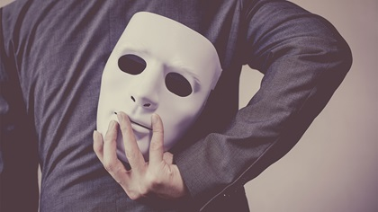 Business person holding anonymous mask behind their back