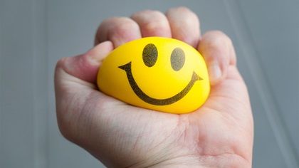 Stressed person squeezing yellow stress ball with a smiley face on it
