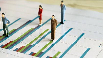 Miniature people toys standing on bar chart
