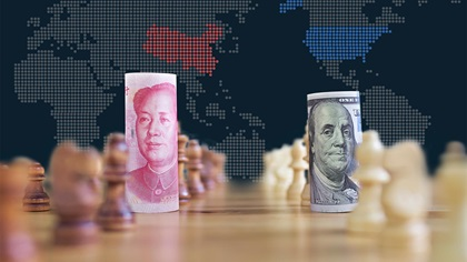 Chinese and US bank notes sitting on chess board