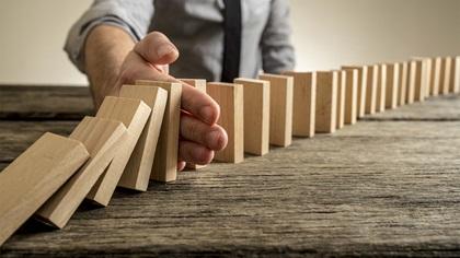 Person disrupting the fall of dominoe blocks