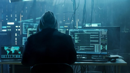 Hacker sitting at computer in a run down IT server room