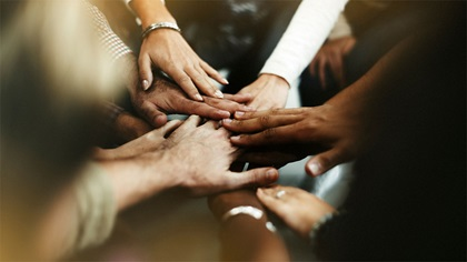 Group of diverse people joining their hands together