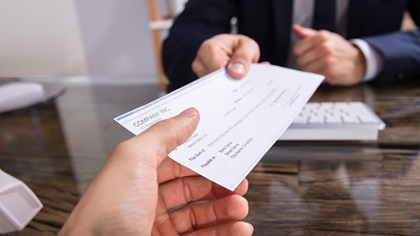 Person handing another person a cheque over a desk