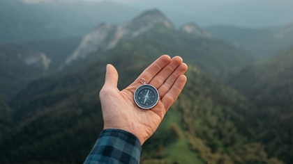 Person holding a compass in their hand whilst on a mountain
