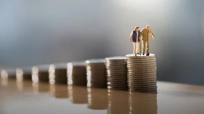 Two elederly people models on top of stacks of coins