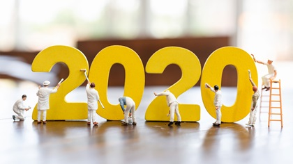 Miniature figurines of workers painting the number 2020
