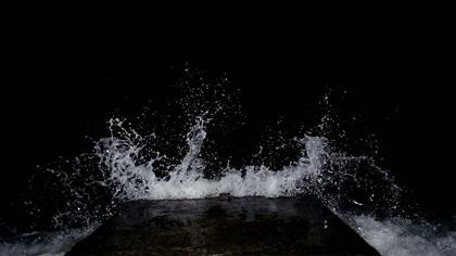 Wave splashing against dark wall at night