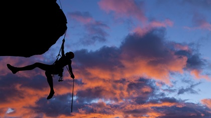 Person rock climbing during sunset