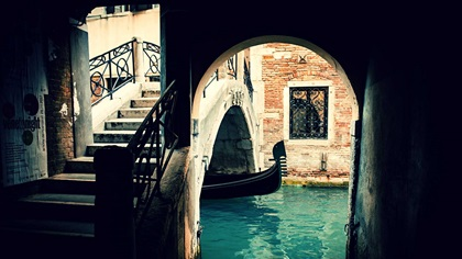 Hidden gondola under a bridge in Venice