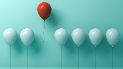 Balloons in a row and a red one raising up