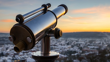 A monocular telescope looking over a town during sunset