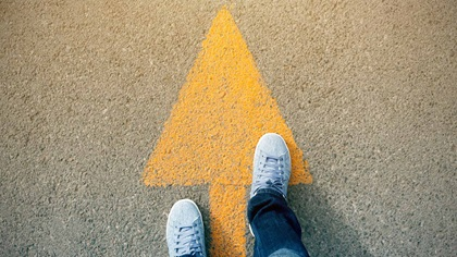Person standing on a yellow arrow painted on the ground, moving forward