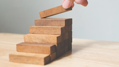 Hand arranging wooden blocks into a staircase