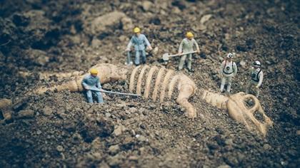 Little toy people discovering dinosaur skellington